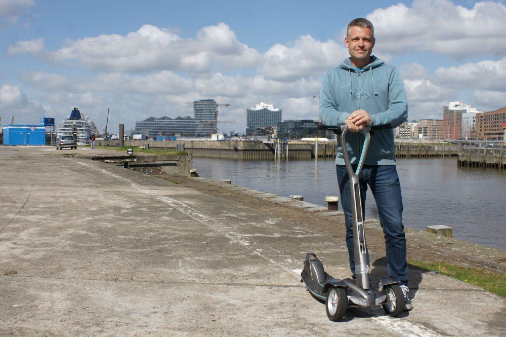 Floatility-Gründer Oliver Risse mit seinem efloater vor der Kulisse der Hamburger Hafencity (Foto: Mathias Jäger)